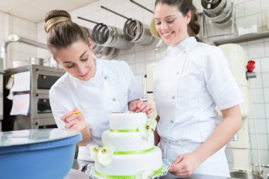 Two pastry bakers decorating large cake