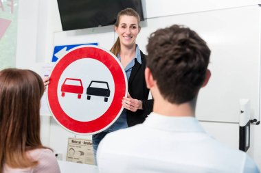 Driving instructor explaining meaning of street sign to class