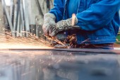 Fotografie Worker in metal factory grinding workpiece with sparks flying