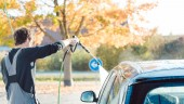 Fotografie Worker cleaning car with high pressure water nozzle
