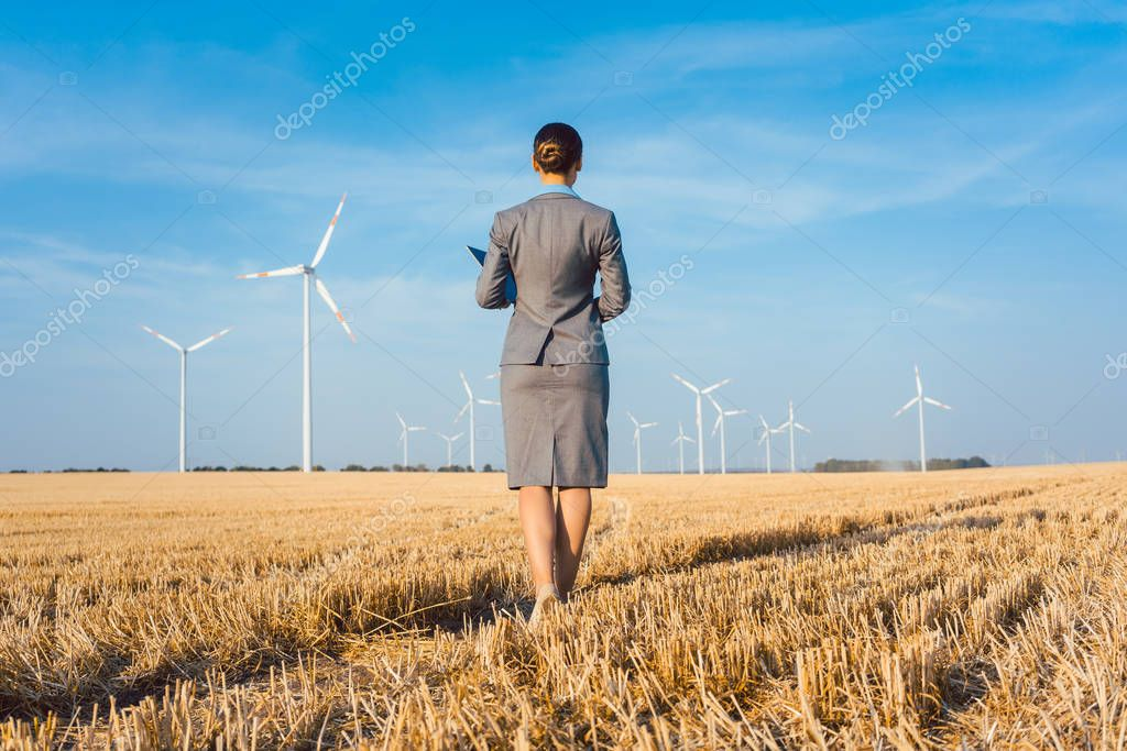 Investor in green energy looking at her wind turbines