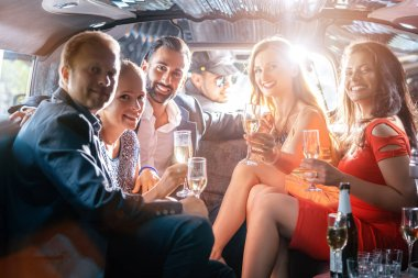 Group of party people in a limo drinking