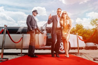 Couple arriving with limousine walking red carpet