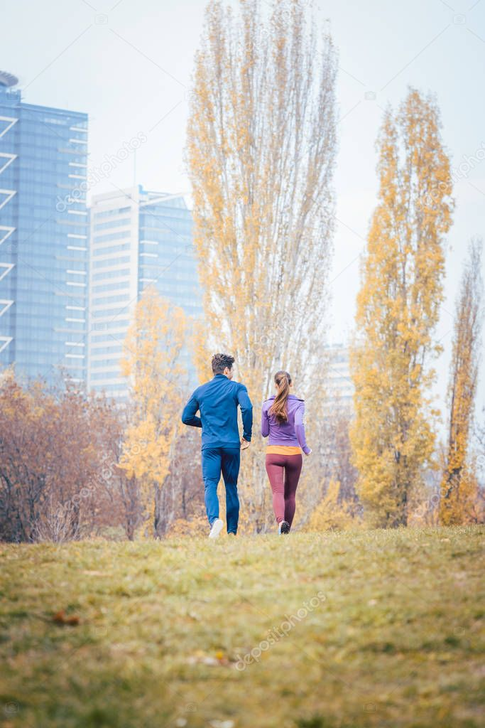 Couple seen from behind running thru a city in fall