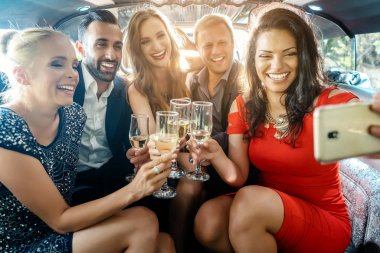 Party people in a limo with drinks taking a selfie with phone