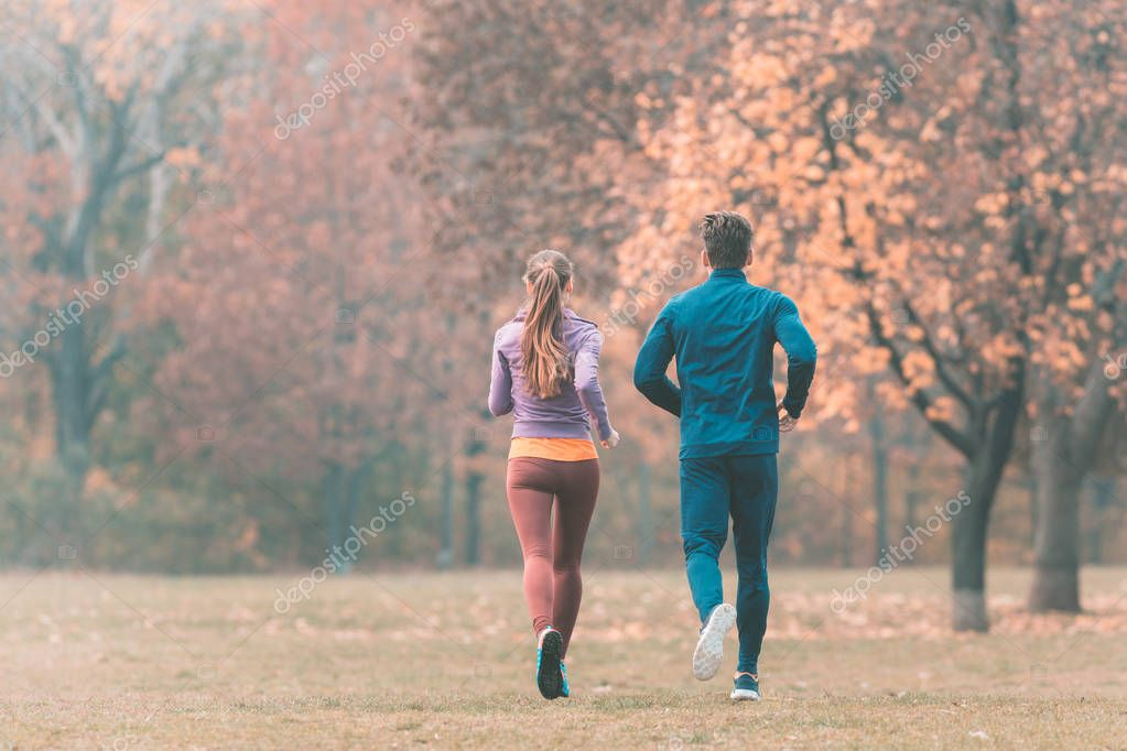 Fall running in a park, seen from behind couple