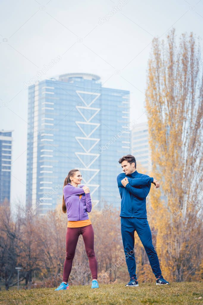 Sport couple doing warm-up exercise before starting a run