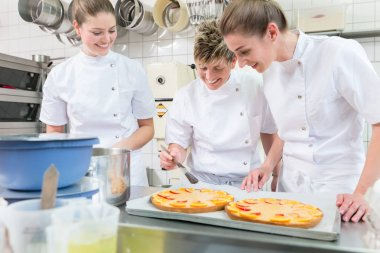 Women putting fruit on cakes in pastry bakery