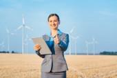 Investor v větrné turbíny s počítačem vyhodnocení její investice