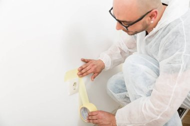 Painter sticking the tape near the plug