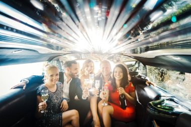 Celebration in a limo, woman and men drinking champagne