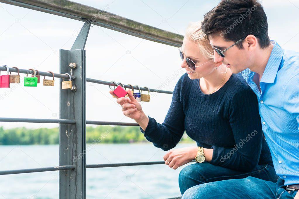 Young couple looking at padlock hang on railing