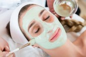 Frau lässt sich im Wellness-Salon von Kosmetikerin pflegen
