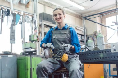 Female mechanic sitting in metal workshop looking into camera