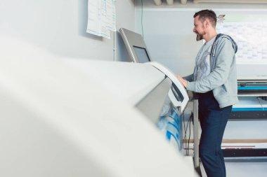 Man working on large format printer in advertising agency