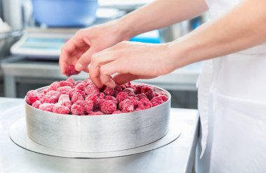 Woman confectioner making raspberry cake