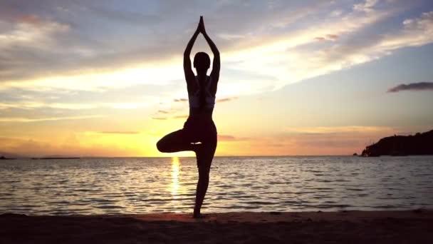Žena cvičí jógu stromu představují na pláži při západu slunce během letních prázdnin