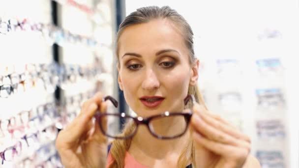 Krásná žena vybrat nové brýle v obchodě