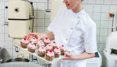 Baker women in pastry bakery working on muffins