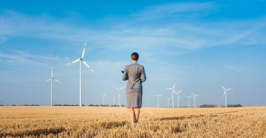 Investor in green energy looking at her wind turbines standing with suit on field stock vector