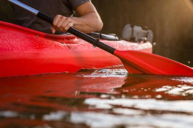Close-up of a man rowing in red kayak using paddle on lake stock vector