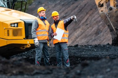 Worker with a plan and a clipboard discussing things in quarry