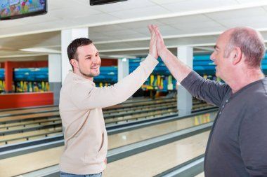 Smiling father and son giving high-five
