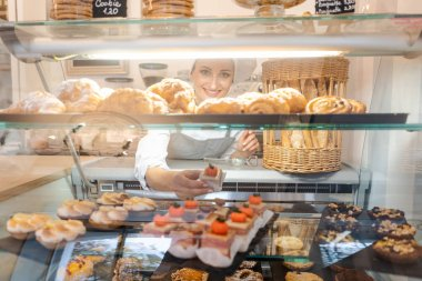 Confectioner shot through glass display in her shop