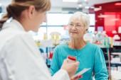 Seniorin in der Apotheke im Gespräch mit Apotheker oder Apotheker