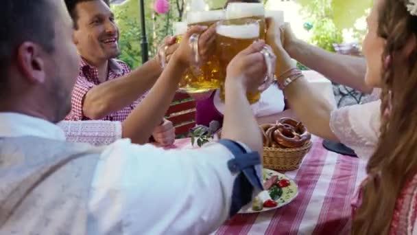 Fröhliche Freunde stoßen im bayerischen Biergarten an