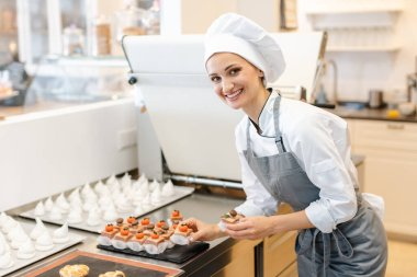 Paitssier putting petite fours on a sheet
