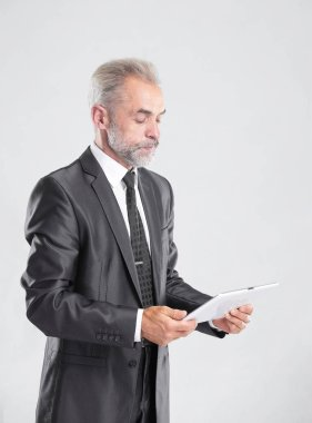 modern businessman reading text on a digital tablet.isolated on grey background