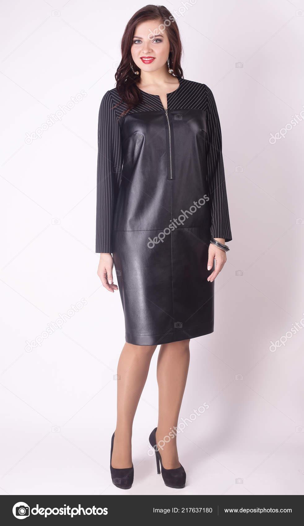 in full growth. modern woman model in a black leather dress .plus ...