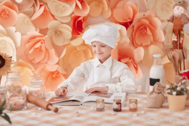 happy boy in a chefs uniform is reading a cookbook