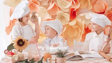 children in uniform chefs standing near the kitchen table.