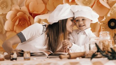happy mother and her child in the form of chefs prepare a festiv