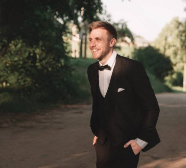 portrait of a happy groom on the background of nature