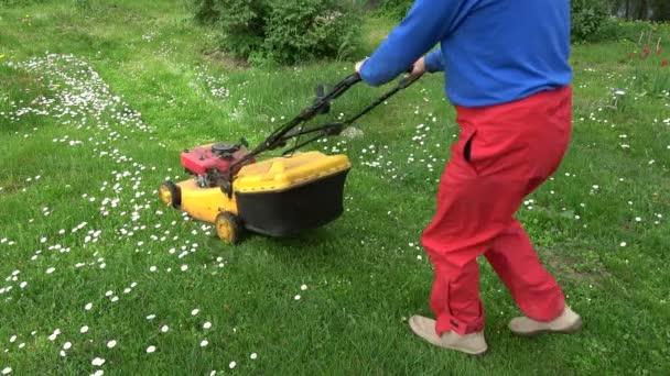 Farmář v zahradě sekat jarní trávy s sekačky