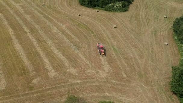 Červený traktor na letní pole hrábě suché seno, letecký pohled