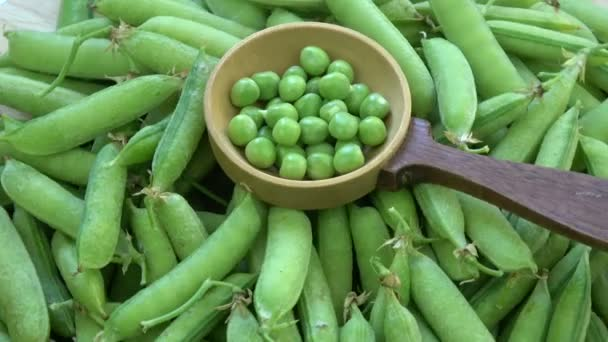 rotierendes Essen Hintergrund - grüne Erbsenschoten und Erbsen in Holzlöffel
