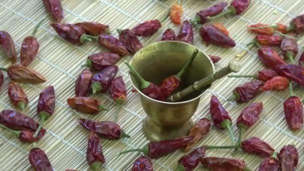 Rotující vintage mosaz Malty paličky s sušených red hot chili papričky na bambusové rohoži