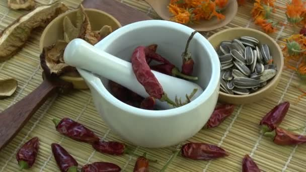 Rotating mortar pestle with  dried chili peppers, medical herbs, sunflowers  and mushrooms on bamboo mat