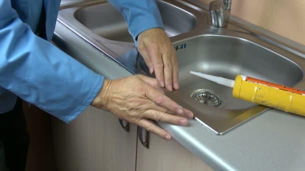 Arbeiterhände fixieren Dichtsilikon-Niveau auf Waschbecken in der Küche