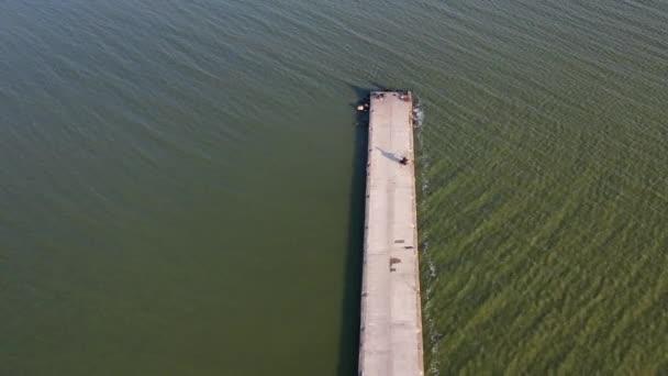 Dlouhé molo vlnolamy na mořské laguně s rybáři, letecký výhled