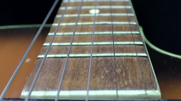 Video of an acoustic guitar neck in perspective. Music and art concept. Black background.