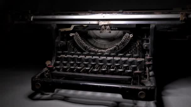 A video camera drives by near an old typewriter on a table in a monotone color.