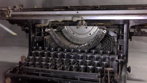 The master greases the old typewriter. A video camera drives by near an old typewriter on a table in a monotone color.