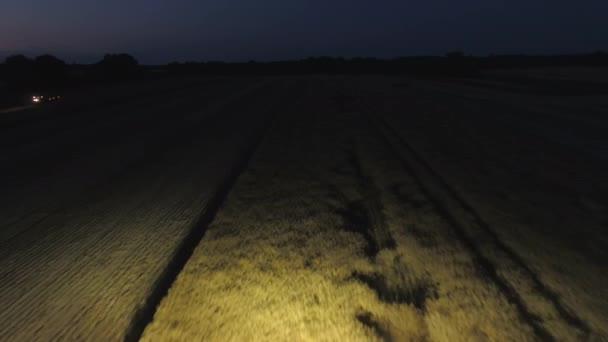 Mietitrebbiatrice lavorando tutta la notte durante il raccolto estivo