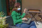 Woman sitting in a garden with antivirus mask looking at laptop