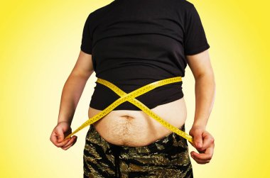 Body of young man with excess weight, keep belly fat in a T shirt, measure itself with a measuring tape on yellow background.